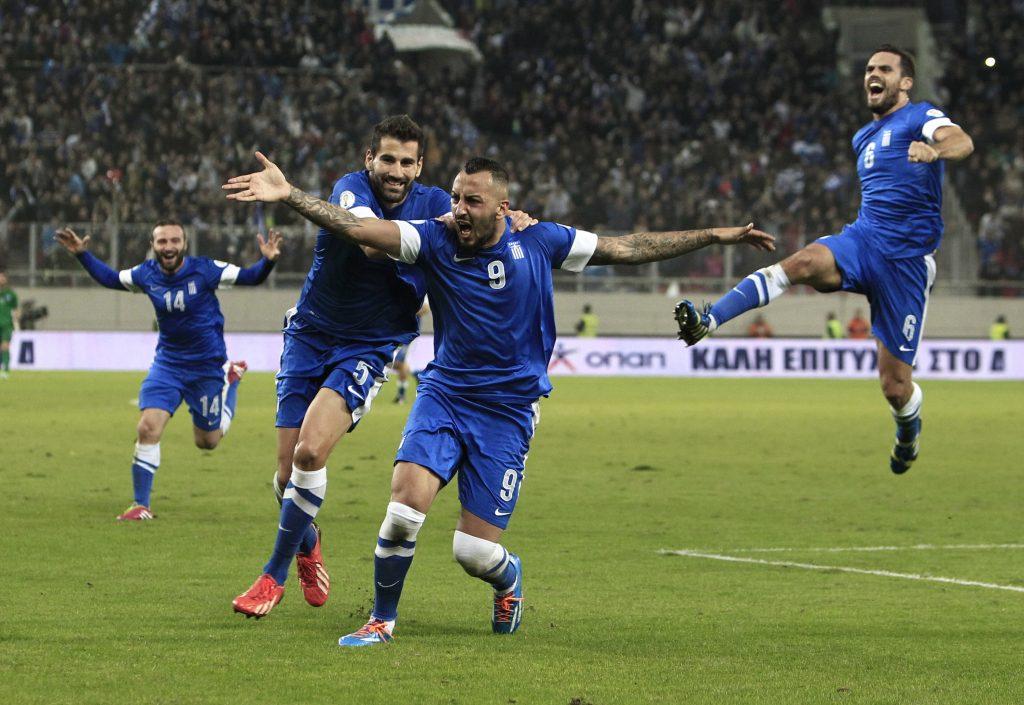 Greece's Kostas Mitroglou, center, celebrates after scoring the third goal of his team against Romania during their World Cup qualifying playoff first leg soccer match at the Karaiskaki stadium in the port of Piraeus, near Athens, Friday, Nov. 15, 2013. (AP Photo/Thanassis Stavrakis)