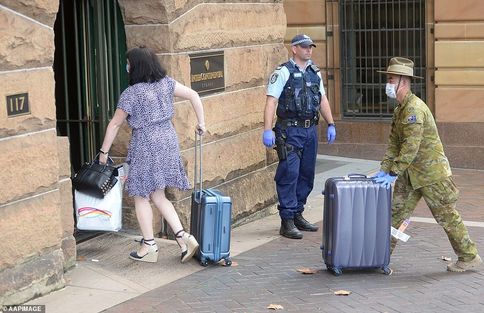 Returning overseas passengers are ushered into their 14-day forced hotel quarantine by members of the Australian Police Force and the Australian Defence Force.