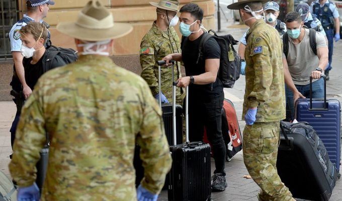 Returning overseas travellers are ushered into Sydney's InterContinental Hotel by the Australian Police and Defence Forces to begin their compulsory 14-day quarantine