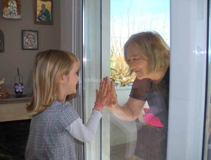 Greek grandparent greeting her grandchild through glass in the covid_19 pandemic