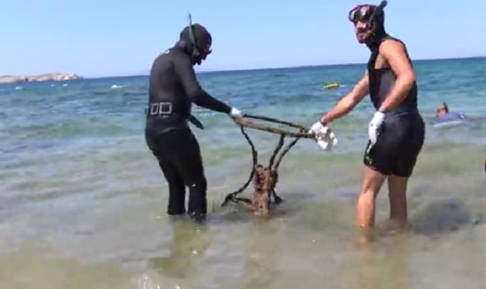 Volunteer divers clean up seabed in front of the iconic Little Venice in Mykonos