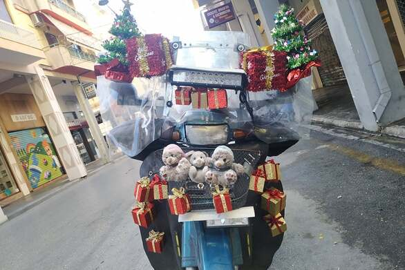 Man in Patras decorates motorcycle with Christmas decorations