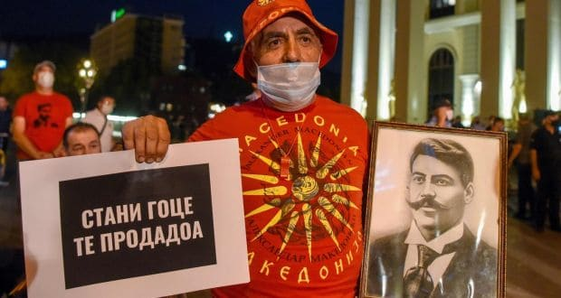 A protester in Skopje wearing a T-shirt with a Greek symbol and holding a photograph of Bulgarian revolutionary figure Goce Delchev and a placard that says 'Get up Goce, they sold you'. Photograph: Robert Atanasovski/AFP/Getty Images