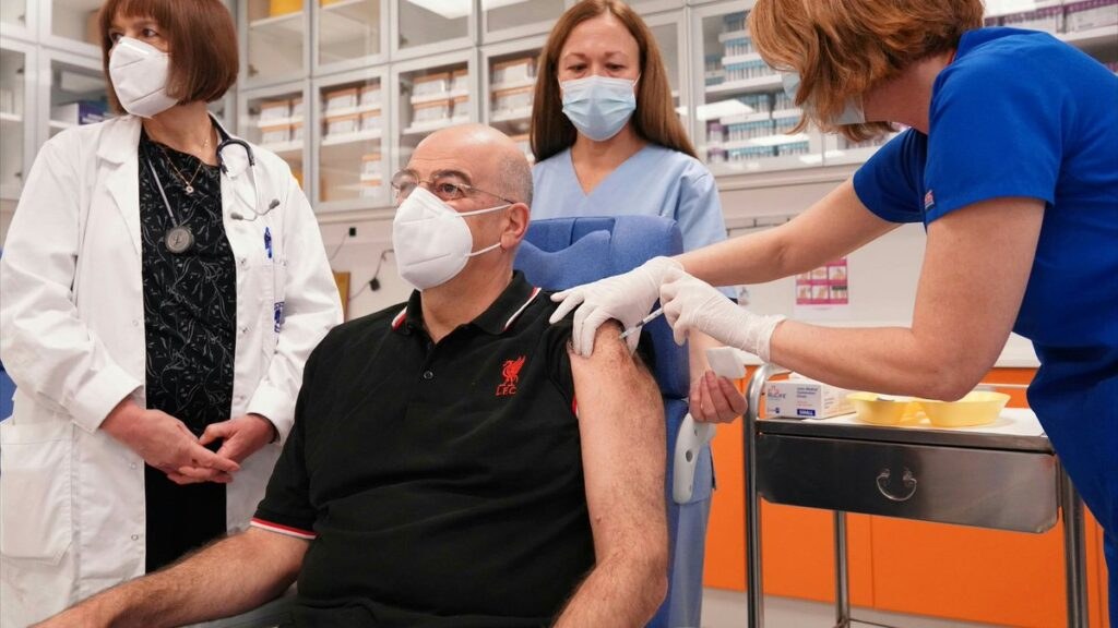 Greek FM Dendias gets COVID vaccine in a Liverpool T-shirt