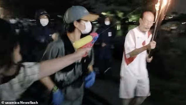 Woman tries to 'shoot' Olympic Flame with water pistol 4